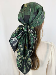 Back view of a classic woman wearing bespoke pom-pom and tassel border Elwyn New York scarf around her head. Print has a mix of vintage entomology motifs and playful, victorian ornamental trim. Sophisticated and fun