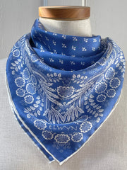 a closeup of a bespoke Elwyn New York bandana tied around the neck of a form like a bib with an ornate, blue and white, vintage-pastoral bandana design. Classic, feminine, and romantic.