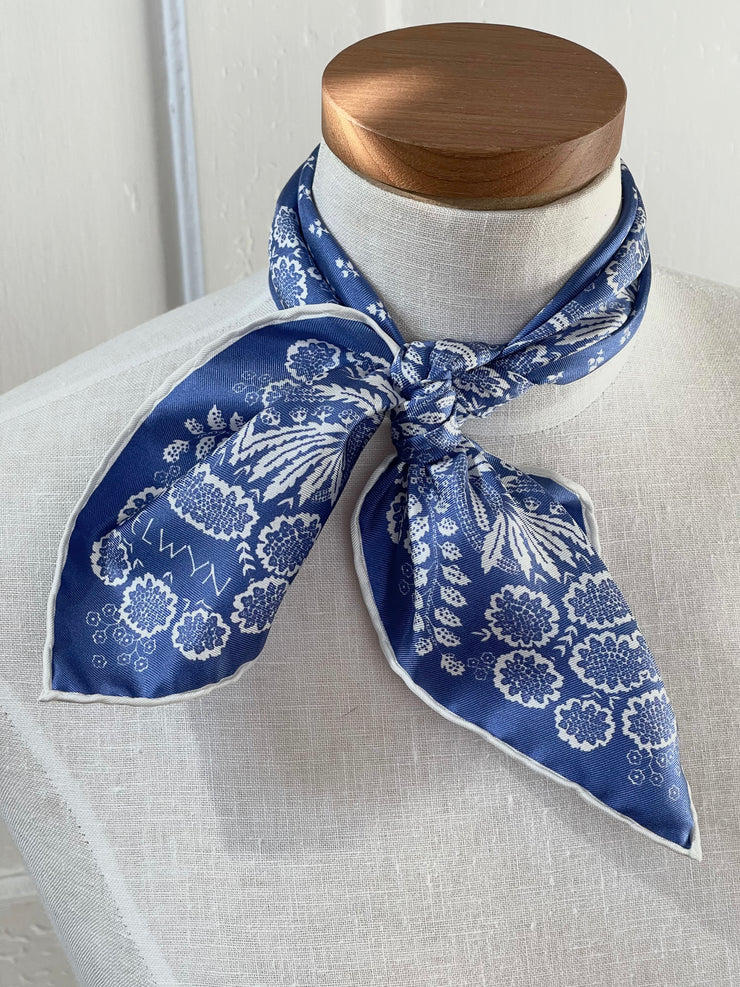 a closeup of a bespoke Elwyn New York bandana tied around the neck of a form with an ornate, blue and white, vintage-pastoral bandana design. Classic, feminine, and romantic.
