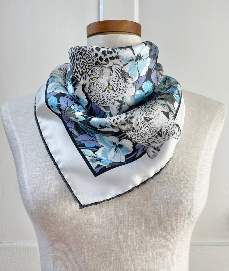 a bespoke Elwyn New York silk bandana, tied around the neck of a form like a bib with vintage style print of a bluish floral field and modern lazing leopards