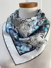 closeup of a bespoke Elwyn New York silk bandana, tied around the neck of a form like a bib with vintage style print of a bluish floral field and modern lazing leopards