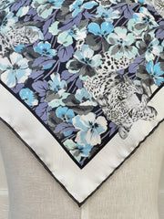 closeup corner of a bespoke Elwyn New York silk bandana, draped on the back of a form with vintage style print of a bluish floral field and modern lazing leopards
