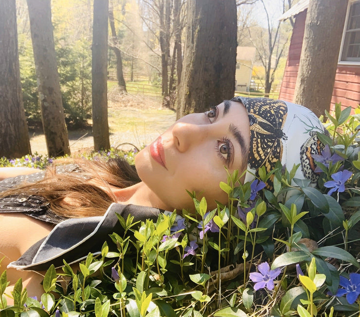 Classic woman, laying in a patch of wildflowers, wearing a luxury, bespoke Elwyn New York silk scarf draped on her head with a vintage style, botanical, floral, butterfly and leopard print