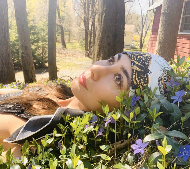 A classic woman laying down in a bed of flowers, wearing a luxury, bespoke Elwyn New York silk scarf on her head with vintage style, botanical, floral, butterfly and leopard print