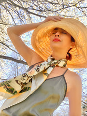 Front view of a classic woman under a flowering tree, wearing a sunhat and luxury, bespoke Elwyn New York silk scarf around her neck with a geometric butterfly vintage modern style print