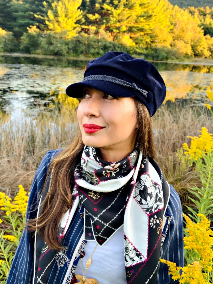 Classic woman standing in front of a lake, surrounded by goldenrod wild flowers, wearing bespoke, luxury Elwyn New York silk scarf loosely looped around her neck. This geometric crazy quilt print is a vintage-modern depiction of the year 2020 filled with digital embroidery and lace of years past.