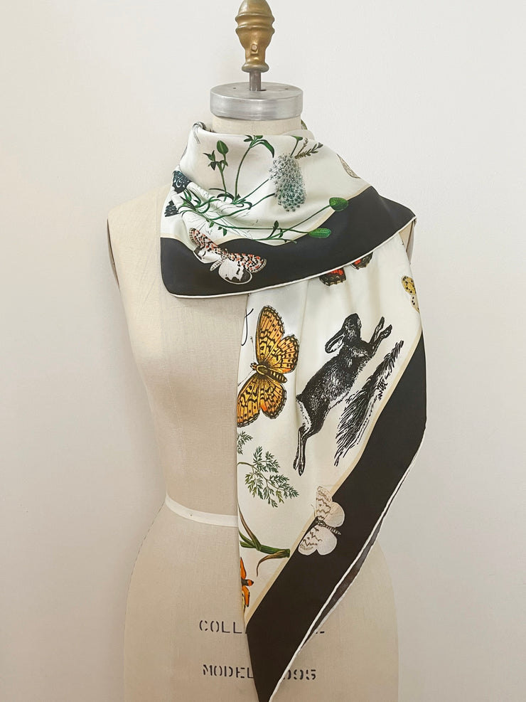 A luxury, bespoke Elwyn New York silk scarf wrapped around the neck of a form with a vintage style, botanical, floral, butterfly and leopard print