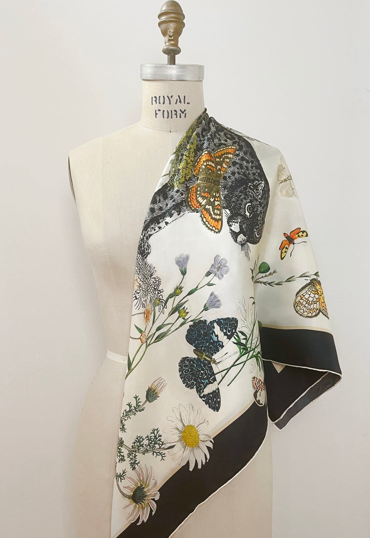 A luxury, bespoke Elwyn New York silk scarf draped on one shoulder of a form with a vintage style, botanical, floral, butterfly and leopard print