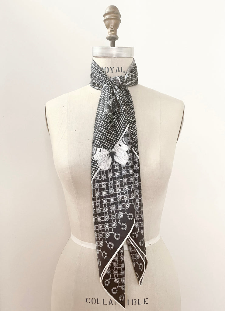 A bespoke luxury, black and white Elwyn New York silk scarf knotted at the front of the neck of a form with butterflies and vintage lace print