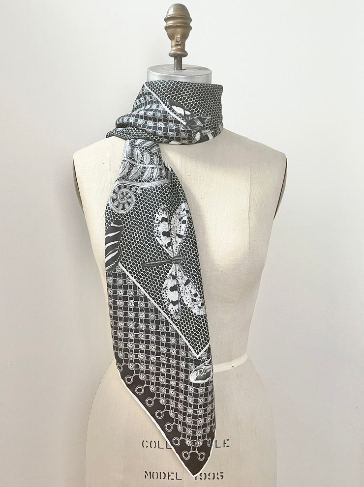 A bespoke luxury, black and white Elwyn New York silk scarf wrapped around the neck of a form with butterflies and vintage lace print