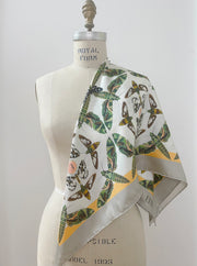 Front view of a luxury, bespoke Elwyn New York silk scarf draped on one shoulder of a form with a geometric butterfly vintage modern style print