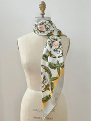 Front view of a luxury, bespoke Elwyn New York silk scarf wrapped around the neck of a form with a geometric butterfly vintage modern style print