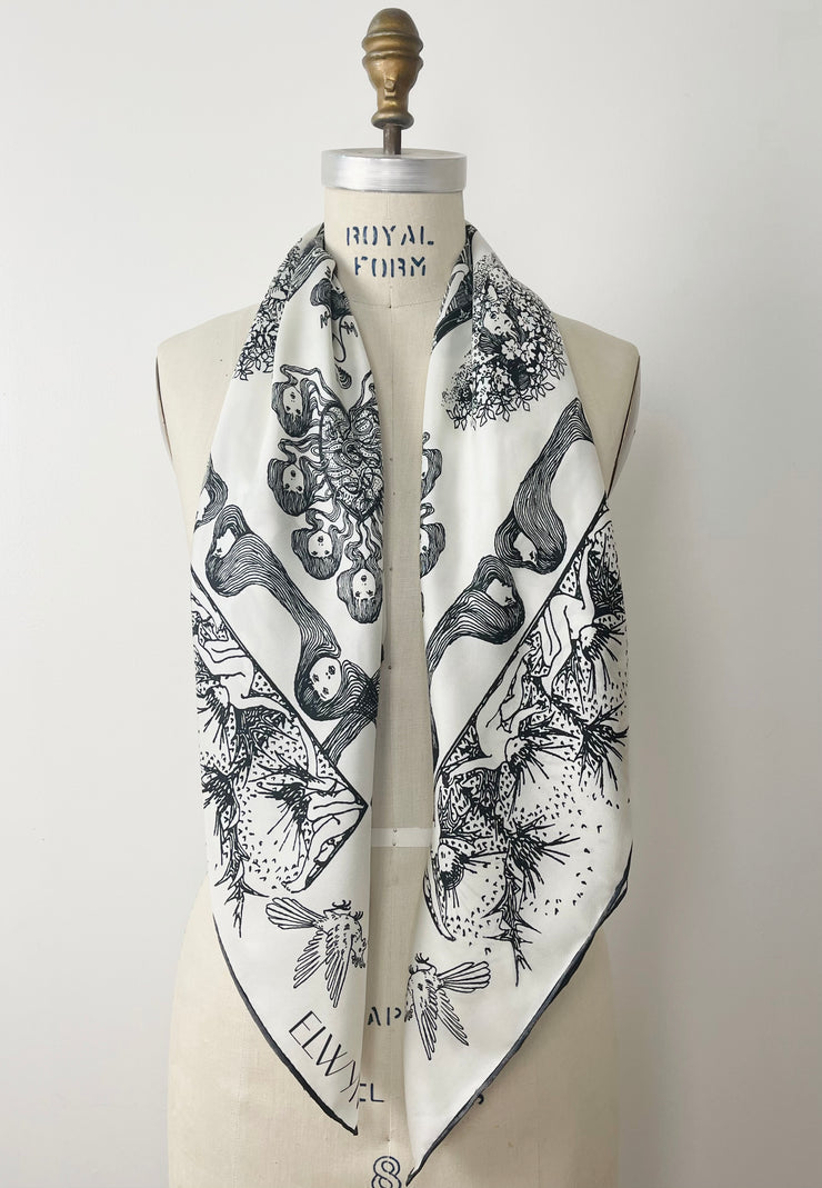 a luxury, bespoke Elwyn New York silk scarf hanging around the neck of a form with black and white, art nouveau, whimsical, storybook print