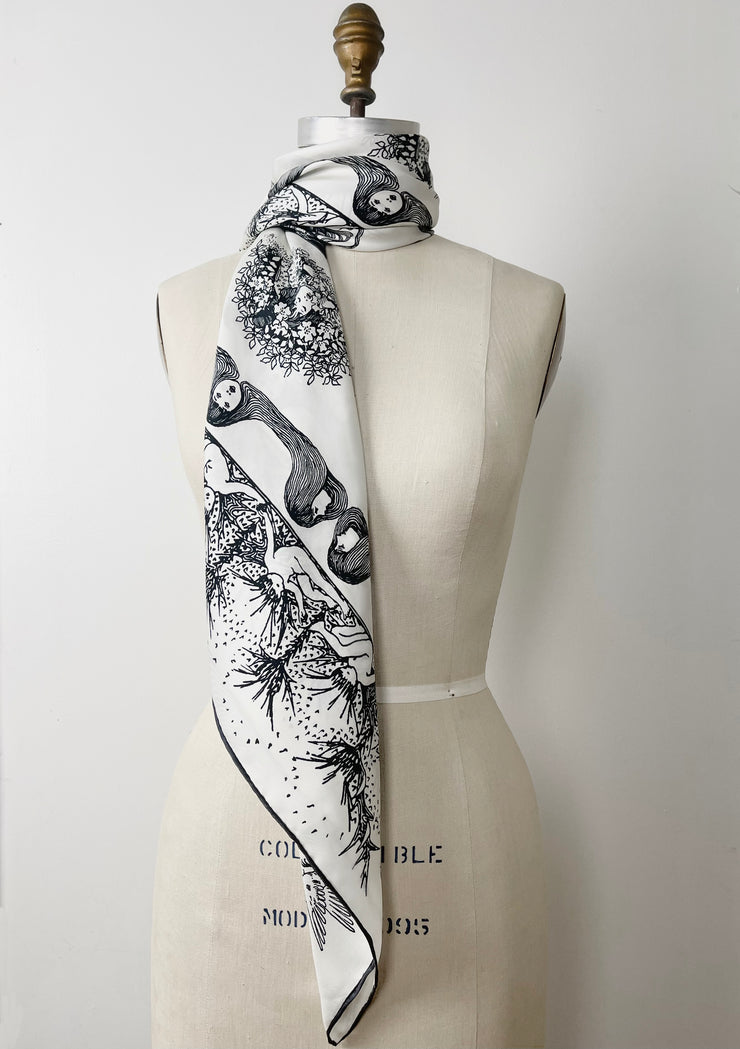 a luxury, bespoke Elwyn New York silk scarf wrapped around the neck of a form with black and white, art nouveau, whimsical, storybook print