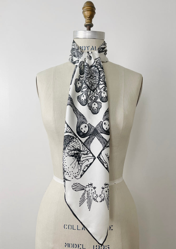 a luxury, bespoke Elwyn New York silk scarf knotted at the neck of a form with black and white, art nouveau, whimsical, storybook print