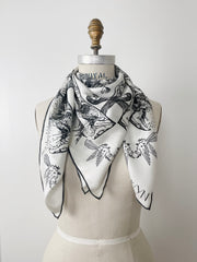 a luxury, bespoke Elwyn New York silk scarf wrapped twice around the neck of a form with black and white, art nouveau, whimsical, storybook print