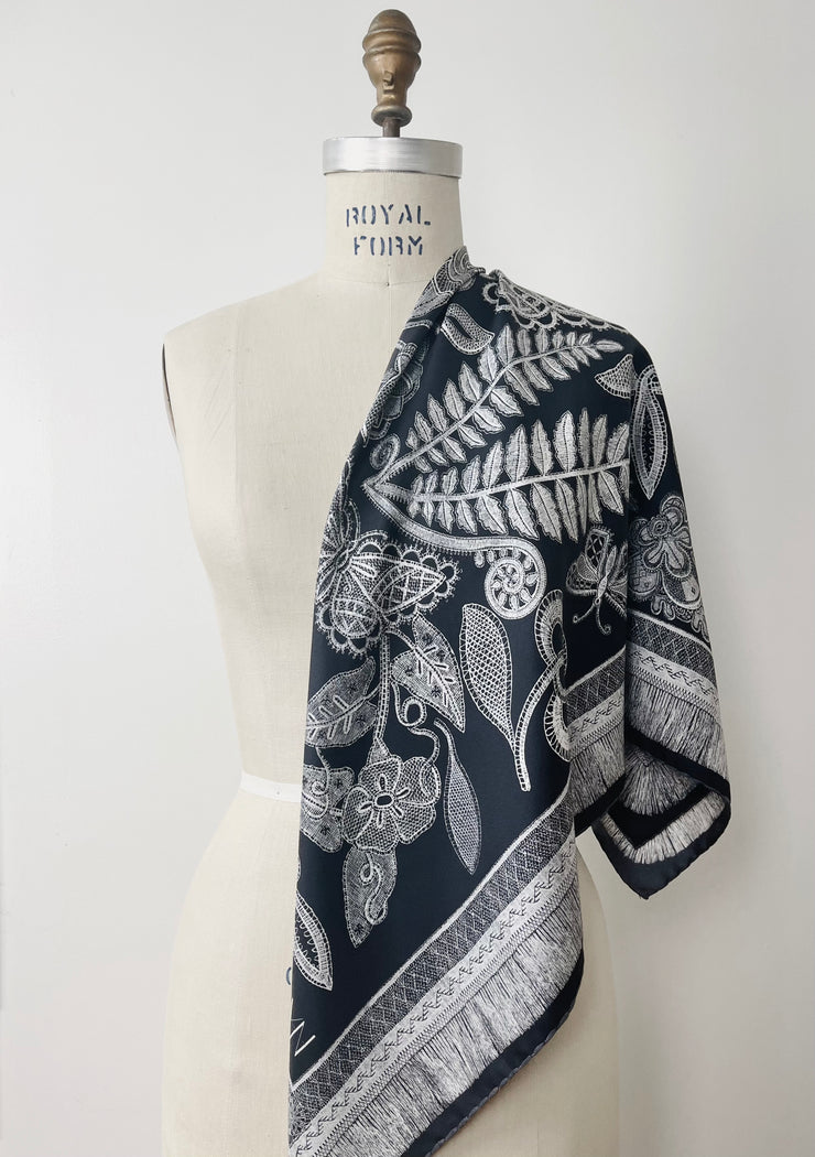 A bespoke, luxury, black and white Elwyn New York silk scarf draped on one shoulder of a form with a vintage lace print and graphic fringe border