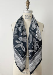 A bespoke, luxury, black and white Elwyn New York silk scarf hanging around the neck of a form with a vintage lace print and graphic fringe border