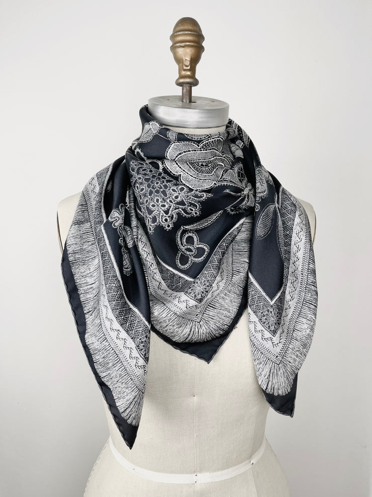 bespoke, luxury, black and white Elwyn New York silk scarf wrapped around the neck of a form with vintage lace print and graphic fringe border