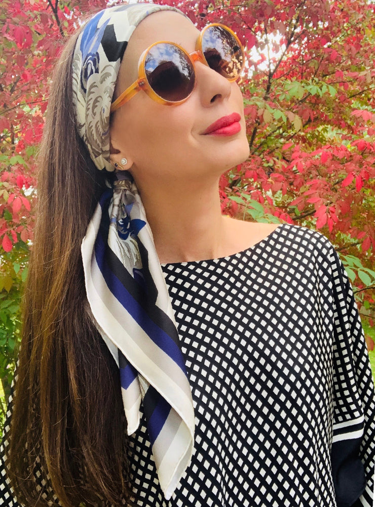 A classic woman standing in front of a red autumn bush, wearing a bespoke, luxury elwyn new york scarf as a headband with a romantic, long side tail . This Denim friendly, zig-zag, art deco floral print feels modern and graphic.
