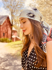 classic woman standing in front a red barn and flowering tree, wearing a luxury, bespoke Elwyn New York silk scarf on her head with black and white, whimsical, polka dot, bird and stars, storybook print