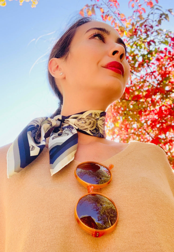 closeup of classic Woman standing amongst the fall foliage, wearing a bespoke, luxury elwyn new york bandana tied in a side bow around her neck. This Denim friendly, zig-zag, art deco floral print feels modern and graphic.