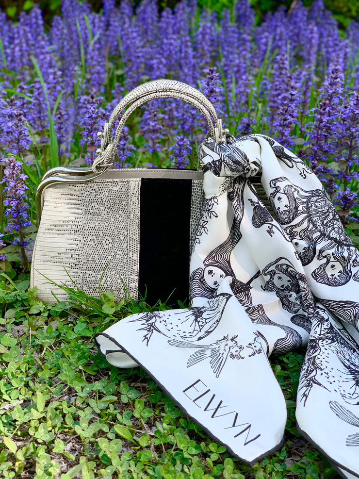 luxury, bespoke Elwyn New York silk scarf draped around her neck with black and white, art nouveau, whimsical, storybook print tied around a vintage handbag set in front a patch of purple wildflowers