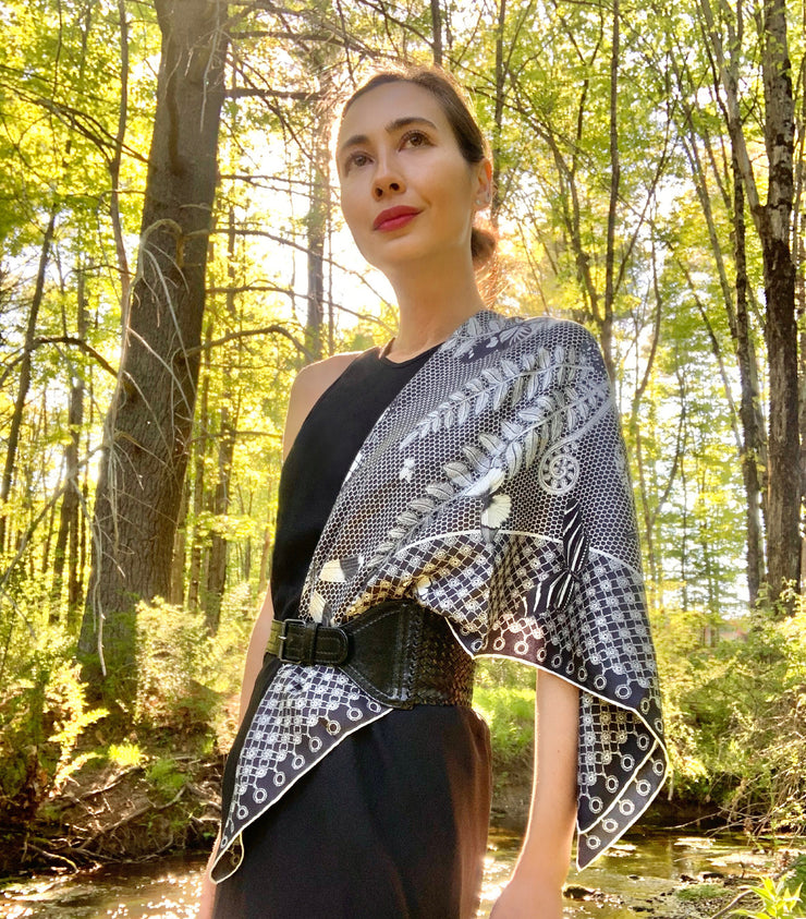 classic woman in the middle of the forest wearing bespoke, luxury, black and white Elwyn New York silk scarf around her neck with butterflies and vintage lace print draped on her shoulder and belted