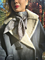 Classic woman standing outside in an autumn jacket, wearing a bespoke Elwyn New York silk scarf loose and looped around her neck with a vintage chain and beaded sautoir print that has intricate, little charm motifs that are strung together in long flowing chains.