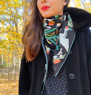 Classic woman standing outside amongst the autumn leaves, wearing bespoke Elwyn New York Scarf draped in a loop around her neck with a botanical crane print is collaged together from antique glass and pearl, beaded embroideries of yesteryear.