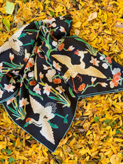 Image of a botanical crane and floral scarf laying in a bed of autumnal yellow leaves.  the print is collaged together from antique glass and pearl, beaded embroideries of yesteryear.