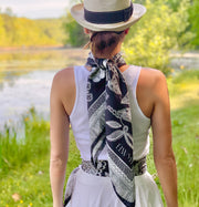 back view of a classic female looking at a pond, wearing bespoke, luxury, black and white Elwyn New York silk scarf around her neck but tied to the back and one tied as a belt. Both have a vintage lace print and graphic fringe border