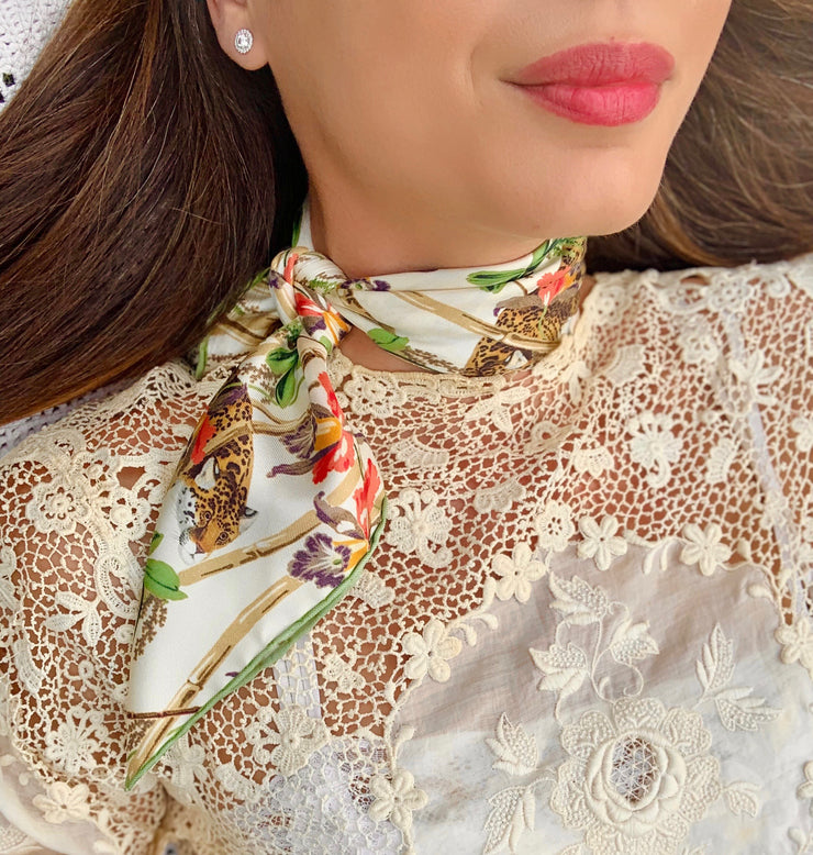 close up of classic woman wearing luxury, bespoke Elwyn New York silk bandana around her neck with vintage tropical, floral, bamboo, leopard wall paper print