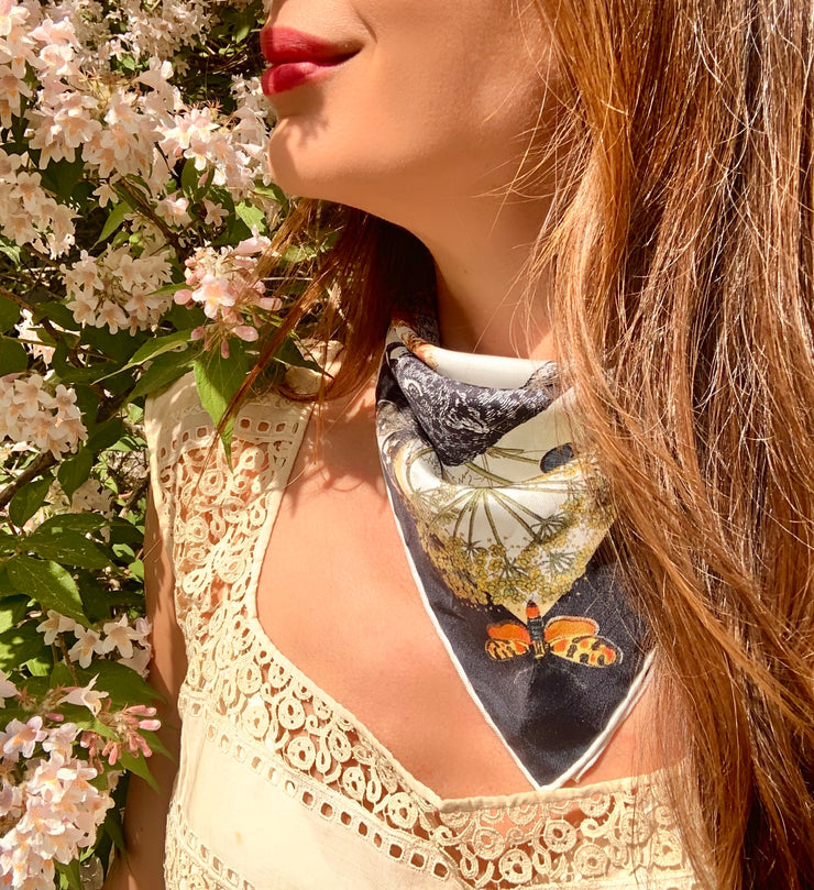 a classic woman standing in a flower bush wearing a luxury, bespoke Elwyn New York silk bandana tied around her neck.  The bandana has a vintage style, botanical, floral, butterfly and leopard print on it