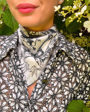 classic woman wearing an Elwyn New York luxury, bespoke Elwyn New York silk bandana with black and white, art nouveau, whimsical, storybook print. She is standing amongst blooming hydrangeas