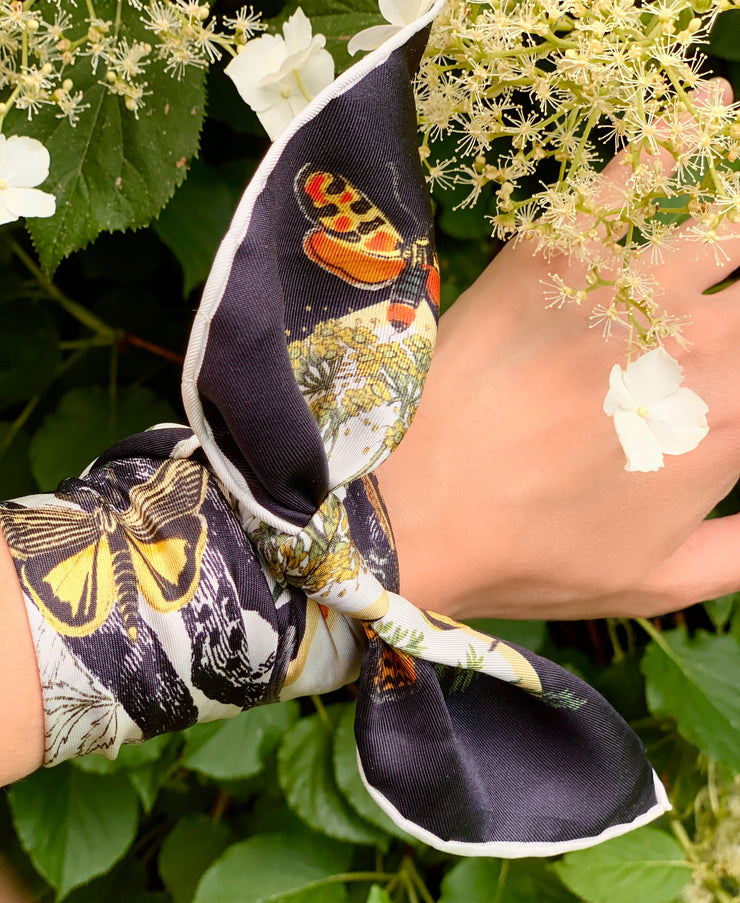 A luxury, bespoke Elwyn New York silk bandana tied around the wrist with a vintage style, botanical, floral, butterfly and leopard print