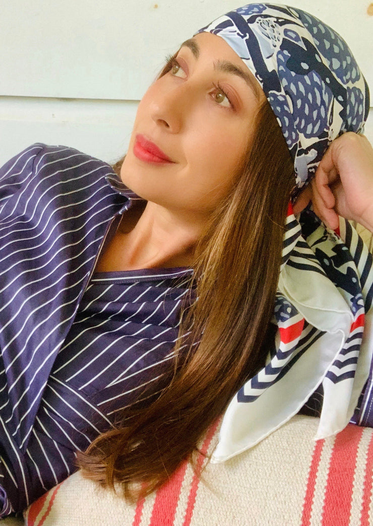 classic woman wearing blue and white, luxury, bespoke Elwyn New York silk scarf on her head with vintage modern deco bird print and striped border lounging on a striped daybed