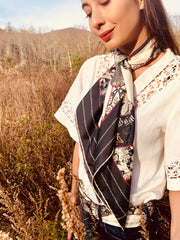 Classic woman standing in a field, wearing bespoke, luxury Elwyn New York silk scarf loosely looped around her neck and a white, antique lace top.  This geometric crazy quilt print is a vintage-modern depiction of the year 2020 filled with digital embroidery and lace of years past.