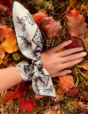 Elwyn New York luxury, bespoke Elwyn New York silk bandana tied around the wrist like a bow with black and white, art nouveau, whimsical, storybook print. Lady's hand resting on a bed of red fall leaves