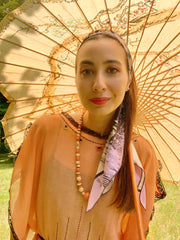 classic woman wearing a luxury, bespoke Elwyn New York silk scarf as a headband with a fierce tiger and pastel lavender, peach, green, black stripe print holding a vintage Chinese parasol, dressed in a 1920's dress