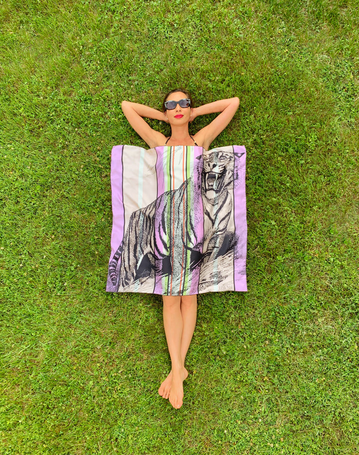 Bird's eye view of classic woman laying in the grass in a bikini with a luxury, bespoke Elwyn New York silk scarf covering her body which has a fierce tiger and pastel lavender, peach, green, black stripe print