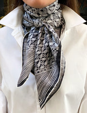 Classic woman wearing a luxury, bespoke, black and white Elwyn New York silk scarf tied around her neck with vintage modern style graphic needlework and crochet print