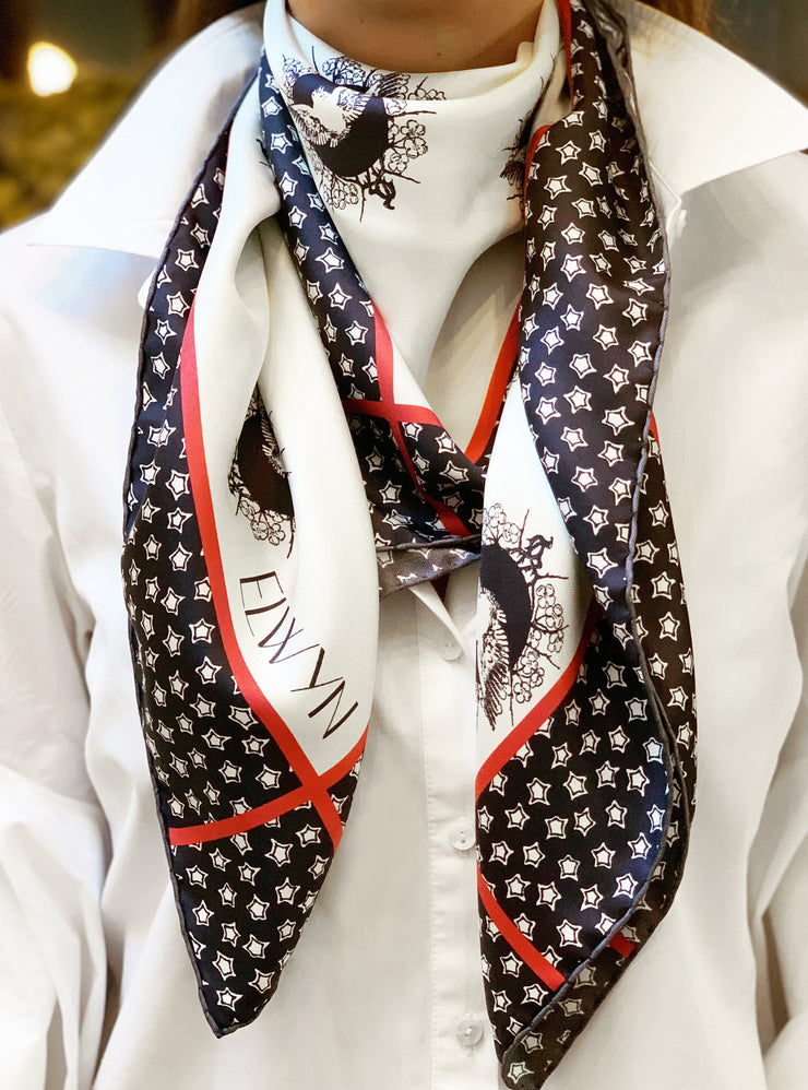 classic woman wearing a luxury, bespoke Elwyn New York silk scarf around her neck with black and white, whimsical, polka dot, bird and stars, storybook print