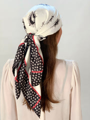 classic woman wearing a luxury, bespoke Elwyn New York silk scarf on her head with black and white, whimsical, polka dot, bird and stars, storybook print