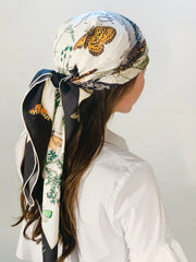 back side view of classic woman wearing a luxury, bespoke Elwyn New York silk scarf on her head  with vintage style, botanical, floral, butterfly and leopard print