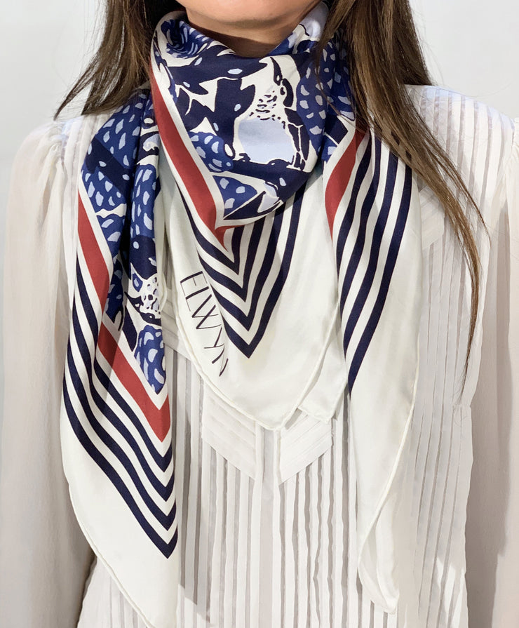 classic female traveler wearing a bespoke, luxury, blue and white Elwyn New York silk scarf around her neck with vintage modern deco bird print and striped border