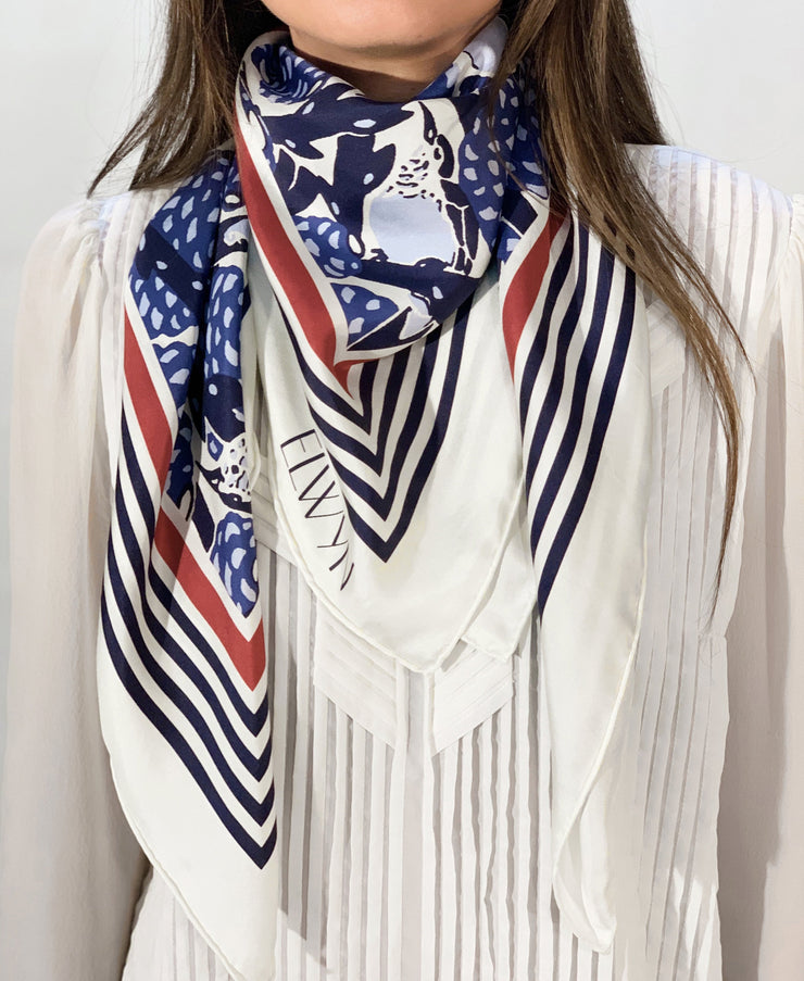 classic female traveler wearing bespoke, luxury, blue and white Elwyn New York silk scarf around her neck with vintage modern deco bird print and striped border