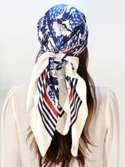 classic woman wearing a bespoke, luxury, blue and white Elwyn New York silk scarf on her head with vintage modern deco bird print and striped border