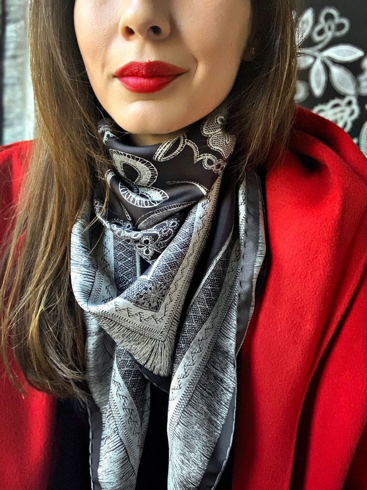 classic female wearing a red coat and bespoke, luxury, black and white Elwyn New York silk scarf around her neck with vintage lace print and graphic fringe border