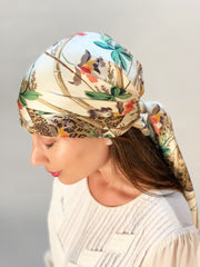 side view of a classic woman wearing luxury, bespoke Elwyn New York silk scarf on her head with vintage tropical, floral, bamboo, leopard wall paper print